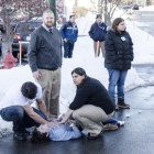 Bystanders assist someone who was pulled from a burning car on Jan. 29.