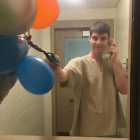 Corey Peterson, through the glass partition visiting area at the Secure Psychiatric Unit at New Hampshire State Prison for Men in Concord. His mother, Shelly Peterson Raza, blew up the balloons and held them up on the visitors' side to make it appear he was holding the balloons to celebrate his birthday Jan. 30. She texted the photo to a relative before guards confiscated her cell phone. Corey has not been charged with a crime.
