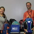 Child Health Services' Becky Martin, left, and Rick Swanson receive23 backpacks full of school supplies from Howe, Riley & Howe in Manchester. Employees from the firm have supported this initiative, which provides the supplies to children in need, for the last three years.