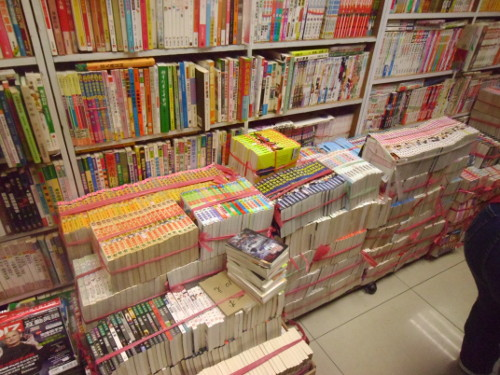 Comic book series bundled together and stacked on upon the other.