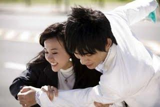 Two characters from the drama are laughing and embracing each other.