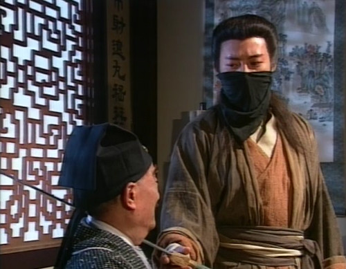 Linghu Chong wears a black cloth covering the lower half of his face as his sword is pointed at a merchant'st throat.