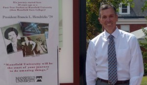 President Fran Hendricks poses with a poster of him during his college days.