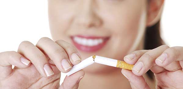 Attractive woman is breaking a cigarette.