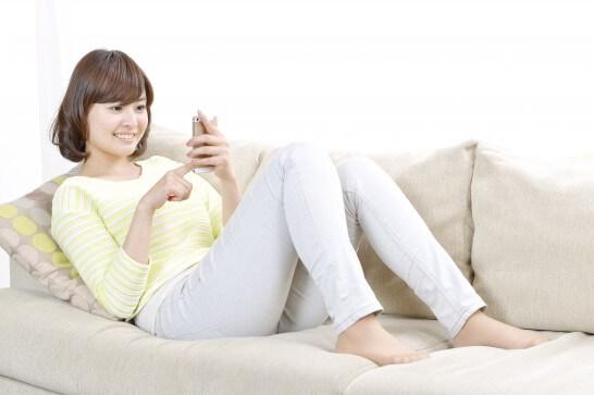 ソファーに座ってスマホを操作する女性
