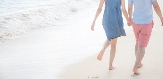 波打ち際を裸足であるくカップル