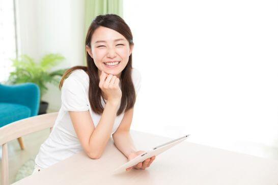 タブレット端末を持つ笑顔の女性