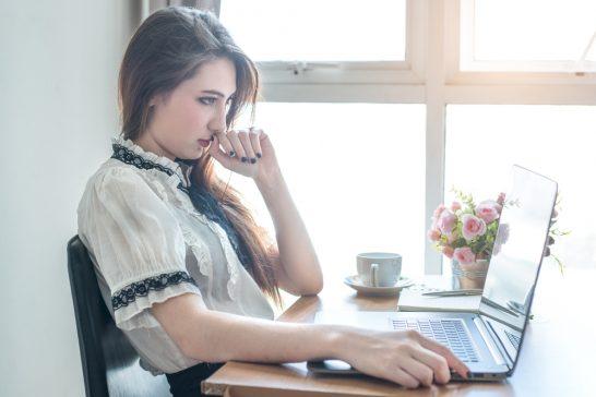 パソコンを見て考える女性