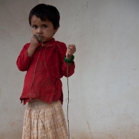 Girl in red with skipping rope, Nepal