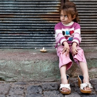 Little girl in rose with mother's shoes