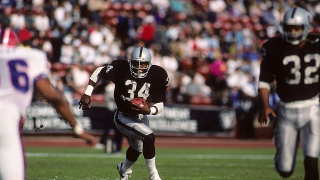 LOS ANGELES - DECEMBER 6:  Running back Bo Jackson #34 of Los Angeles Raiders follows the lead of teammate Marcus Allen #32 agains the Buffalo Bills defense during the game at the Los Angeles Memorial Coliseum on December 6, 1987 in Los Angeles, California.  The Raiders won 34-21. (Photo by George Rose/Getty Images)