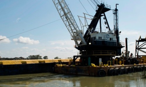 Rock removal from a barge in the West False River in the Sacramento-San Joaquin Delta in Contra Costa county to construct the 750-foot-wide rock barrier to help deter the tidal push of saltwater from San Francisco Bay into the central Delta. Photo taken on May 8, 2015.