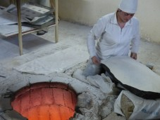 After throwing the dough from one hand to another to make it thinner, it is then spread on a cushion.