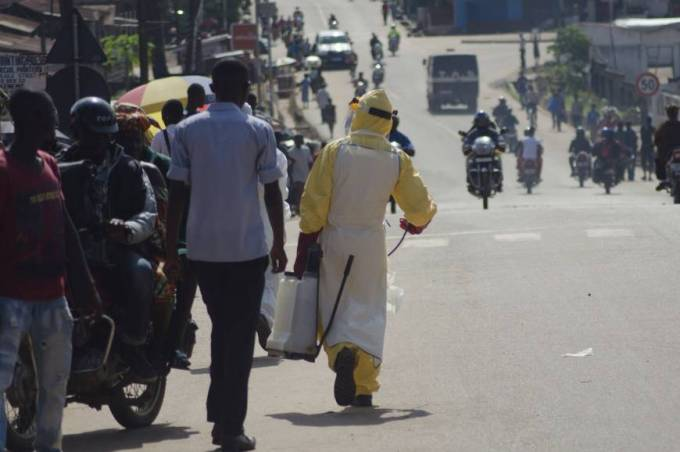 A health worker with disinfectant spray walks down a street outside the government hospital in Kenema, Sierra Leone, on July 10. Ebola has killed 632 people across Guinea, Liberia and Sierra Leone since an outbreak began in February, putting strain on a string of weak health systems facing one of the world's deadliest diseases despite waves of international help. | REUTERS