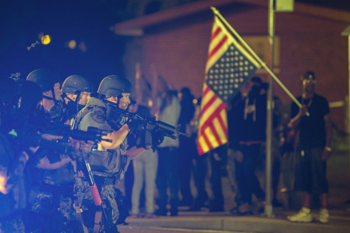A police officer raises his weapon at a car speeding in his general direction as a more vocal and confrontational group of demonstrators stands on the sidewalk during further protests in reaction to the shooting of Michael Brown near Ferguson, Missouri August 18, 2014. Police fired tear gas and stun grenades at protesters in Ferguson, Missouri on Monday, after days of unrest sparked by the fatal shooting of an unarmed black teenager by a white policeman. REUTERS/Lucas Jackson