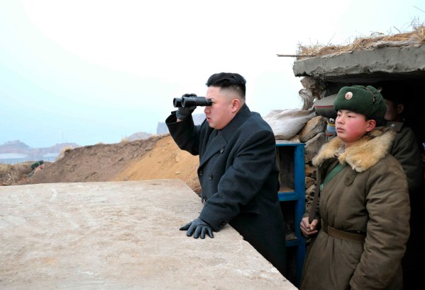North Korean leader Kim Jong-Un (C) uses a pair of binoculars to look towards the South, near the border with South Korea, southwest of Pyongyang March 7, 2013.