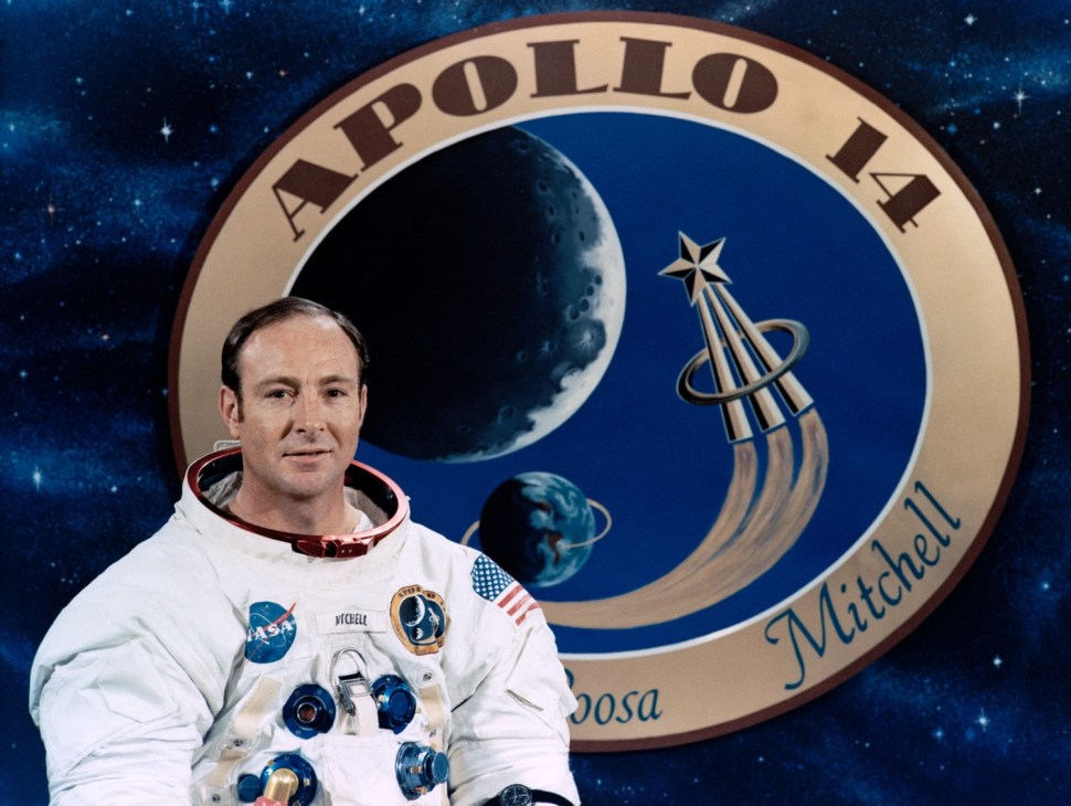 Apollo astronaut Edgar Mitchell in front of a graphic of the mission patch. [NASA]