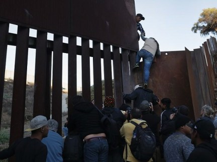 TIJUANA, MEXICO - DECEMBER 02: A woman climbs atop a fellow member of the migrant caravan while crossing over the U.S.-Mexico border fence on December 2, 2018 from Tijuana, Mexico. Numerous members of the caravan were able to pass from Tijuana to San Diego and were quickly taken into custody …