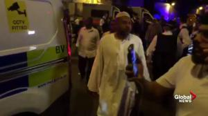 Stream of worshippers leave mosque from behind police barricade after reported vehicle attack in UK
