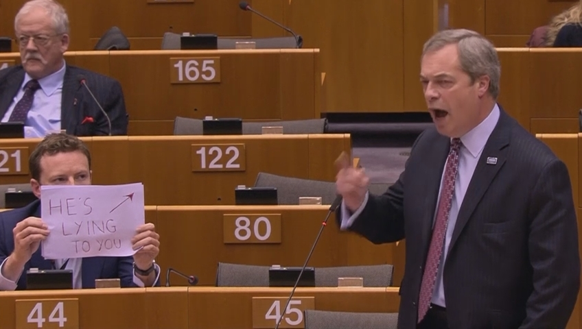Gay MEP holds up 'he's lying' sign behind Brexit leader Nigel Farage