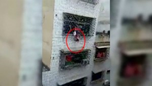 Girl dangles by her head out of a fourth-storey window