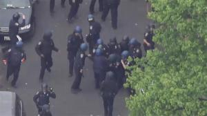 Aerial footage: Wounded police officer helped to armoured car during violent street clashes in Baltimore