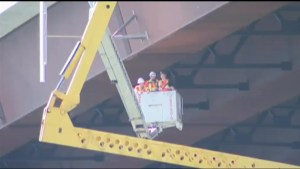 Two men trapped after crane topples over the side of a bridge in Rhode Island