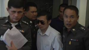 Police escort Thai doctor away after woman dies during cosmetic surgery