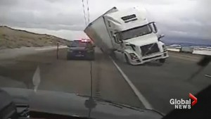 Wind gust pushes tractor trailer onto police patrol car