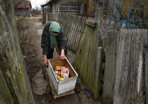 Ekaterina Kozel pulls a trolley with food to her house in the almost abandoned village of Tulgovichi, near the 18-mile exclusion zone around the Chernobyl nuclear reactor. // Sergei Grits / AP