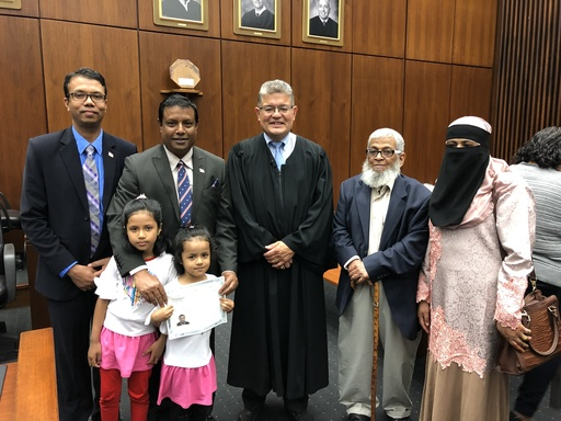 A man stands alongside a judge and his family at his naturalization ceremony.