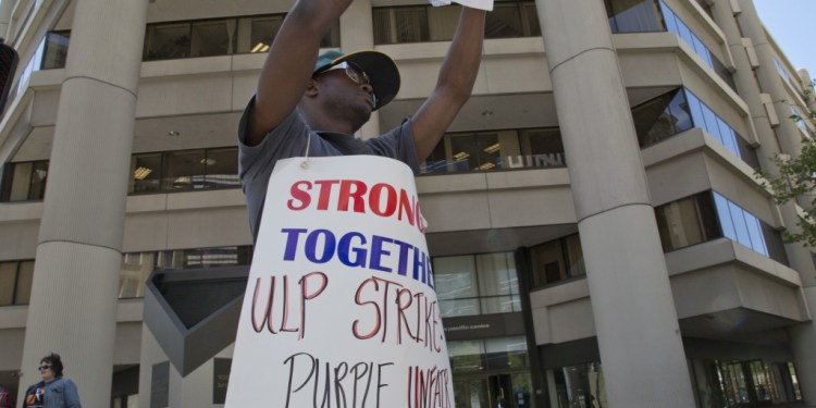 Anthony Brown, American sign language interpreter, is part of a one-day strike against Purple Communications in Oakland. Photo by David Bacon 2014.