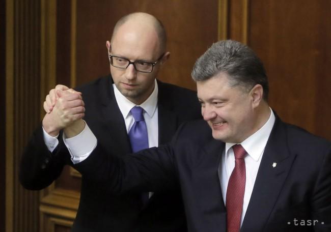 Ukrajinský prezident Petro Porošenko (vpravo) a ukrajinský premiér Arsenij Jaceňuk reagujú na ustanovujúcej schôdzi ukrajinského parlamentu, ktorý vzišiel z októbrových volieb, v Kyjeve 27. novembra 2014. (TASR)