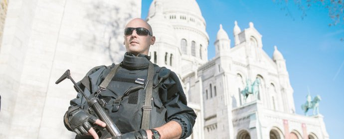 A French police officer patrols at the Sacre Coeur basilica in Paris, Sunday, Nov. 15, 2015. Thousands of French troops deployed around Paris on Sunday and tourist sites stood shuttered in one of the most visited cities on Earth while investigators questioned the relatives of a suspected suicide bomber involved in the country's deadliest violence since World War II. (AP Photo/Kamil Zihnioglu)