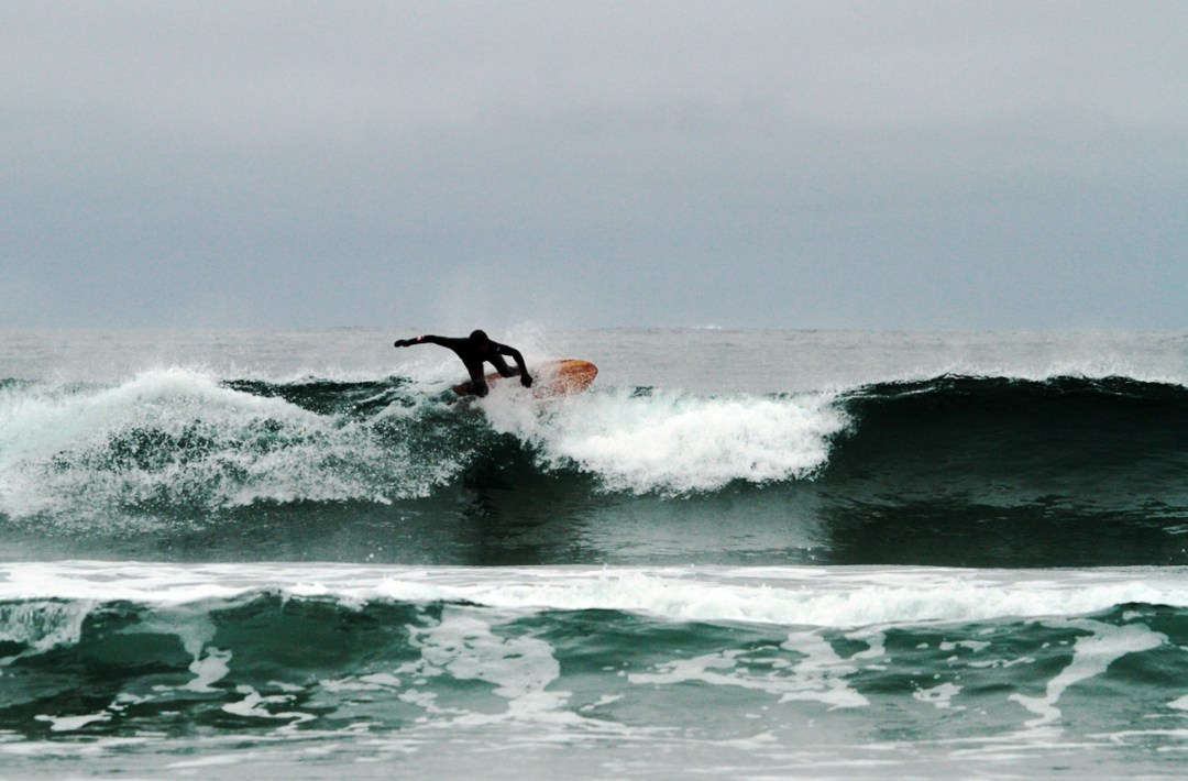Raph Rruhwiler riding a Wefi board in Tofino. Photo By Adam Dewolfe.