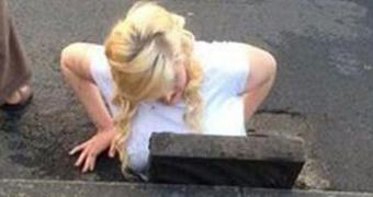 Moça de cabelo claro fica presa em bueiro tentando resgatar celular