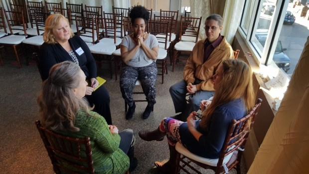 Kelly, center with hands at chin, participating in small group work at the Swarm.