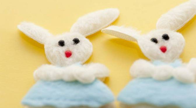 Two fluffy Easter bunnies in blue clothes, flat decorative needlework pieces on yellow