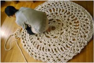 Девушка вяжет коврик