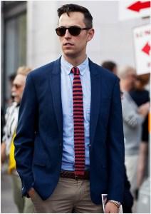 Парень в костюме и в вязаном полосатом галстуке