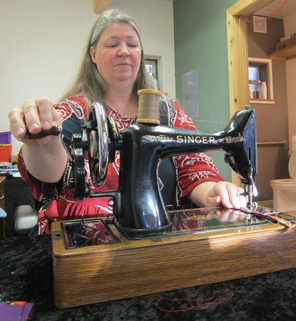 Taera Jones uses a vintage Singer sewing machine in her new shop, Looney Creek. Photo by Don Nelson