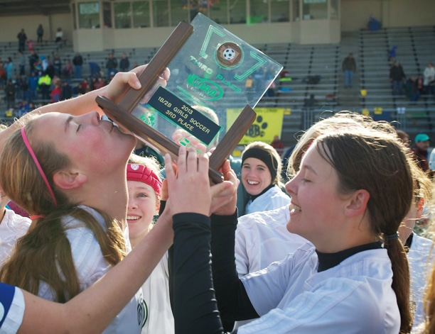 Senior co-captain Kathleen Chavey-Reynaud kisses the third-place trophy – with assistance from Tabitha Bergiven-Krumme – that the Lady Lions soccer team captured at last weekend's state championships. Photo by E.A. Weymuller