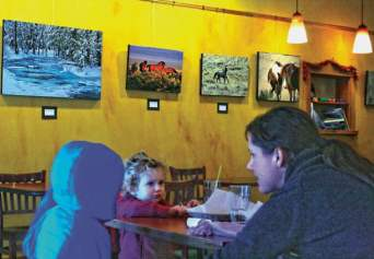 Janelle Delfino and her daughter Gillian Kipp enjoy a treat at Cinnamon Twisp, which exhibits original artwork to support artists and enhance the atmosphere at the bakery.Photo by Marcy Stamper
