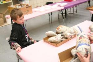 Brody awaits assistance with the process of attaching limbs to the body of his critter. Photo by Darla Hussey