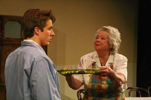 Emma (Jane Pappidas) tempts her grandson, Nick (Ray Sanders), with a plate of antipasto in the comedic family drama. Photo by Marcy Stamper