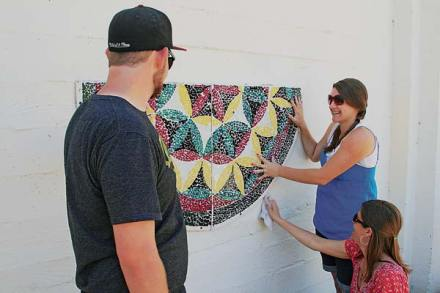 ILC seniors Nate Mowen, left, and Julie McMillan, in blue, helped mount the flower-of-life mosaic on the Community Center wall, assisted by teacher Kim Odell. Students at the school selected Mowen's color scheme for the final artwork, which will be the centerpiece for a memory garden at the Community Center. Photo by Marcy Stamper