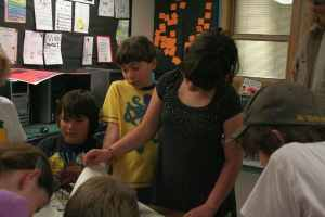 From left, Zyan, Alex, Dalyn look at 100 year old newspapers. Photo by Darla Hussey