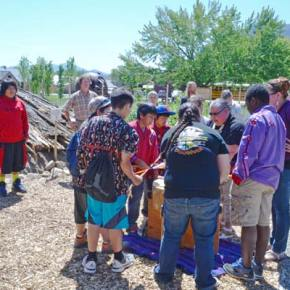 Michelle Matt and Tashina Gorr lead a group of Paschal Sherman Indian School students in drumming and song beside the newly completed pit house at the Methow Valley Interpretive Center in Twisp. Photo by Laurelle Walsh