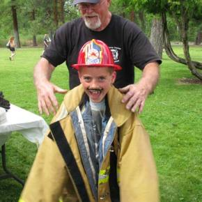 Volunteer firefighter Dick Evans helps an aspiring firefighter try on the gear. Photo by Pat Leigh