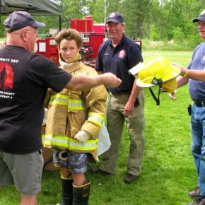 Lazo Gitchos, center, potential volunteer firefighter recruit, got the full treatment from volunteer firefighter Dick Evans, left, volunteer Captain John Owen, and Fire Chief Don Waller, far right.Photo by Pat Leigh